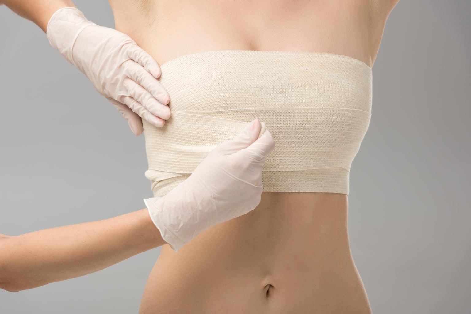 Efter bröstreduktion, kvinna med bandage runt brösten